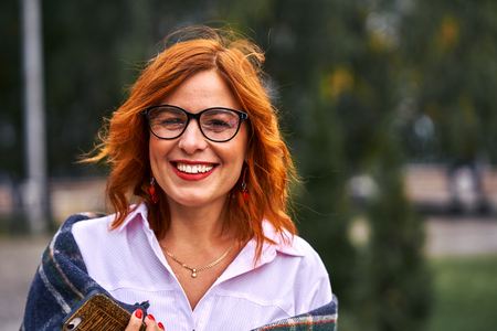 Portrait of a beautiful smiling middle-aged woman with red hair wearing glasses on a cloudy day. Close-up. Standard-Bild