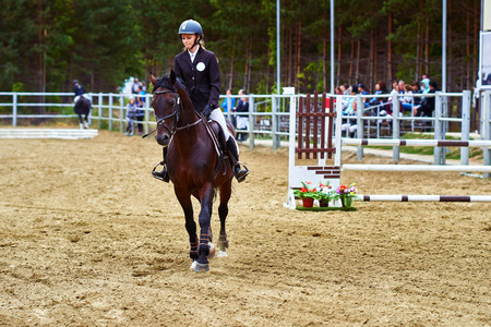 Young woman jockey in white black dress and black boots, takes part in equestrian competitions.