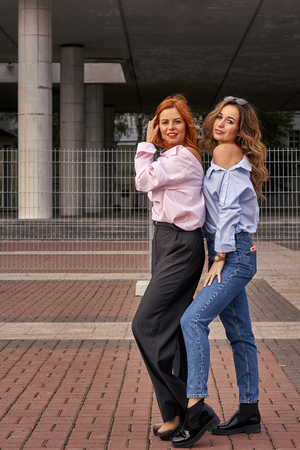 Two beautiful women with red and brown hair walk around the city on a cloudy autumn day. Stok Fotoğraf