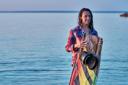 A middle-aged woman has finished wakesurfing on a big river on a summer evening at sunset.