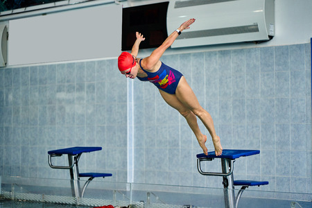 Female athlete jumps to the pool water. Middle-aged woman professionally engaged in swimming. Archivio Fotografico