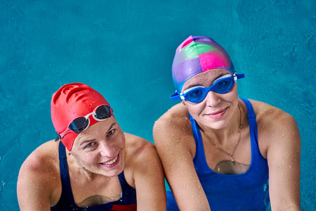 Two smiling swimmer women relaxing in the pool after a swim. Close-up.