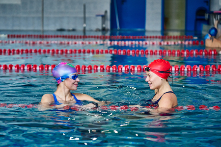 Two smiling swimmer women relaxing in the pool after a swim. Фото со стока