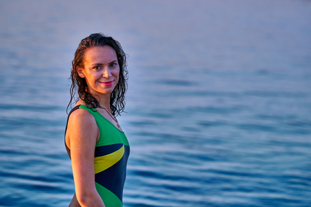 Portrait of a black-haired wet middle-aged woman in a swimsuit on a summer evening in the light of the setting sun. Stok Fotoğraf