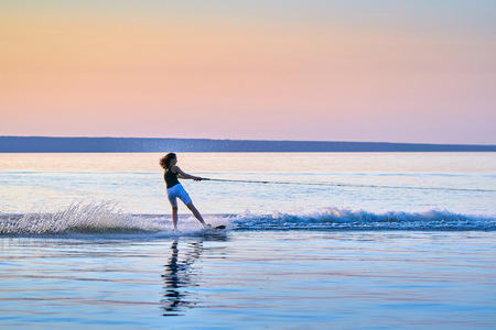 Woman surfer with black hair rolls on the board on a flat surface of water in the summer sunny evening.