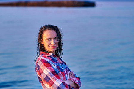 Portrait of a black-haired wet middle-aged woman in a plaid shirt on a summer evening in the light of the setting sun.