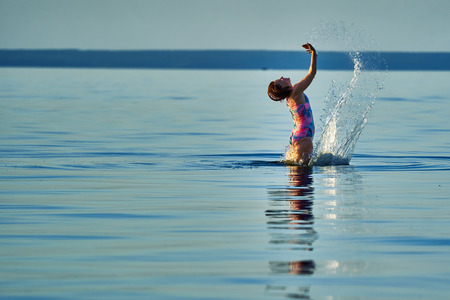 A middle-aged woman with red hair and a swimsuit bounces in the water of a large lake on a quiet summer sunny evening. Banque d'images - 120536429