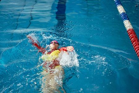 Vrouwelijke atleet in een rood-gele zwembroek zwemt op zijn rug. Waterspatten verspreiden zich in verschillende richtingen.