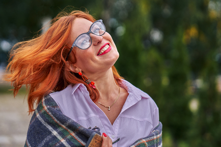 Portrait of a beautiful smiling middle-aged woman with red hair wearing glasses on a cloudy day. Close-up. Фото со стока