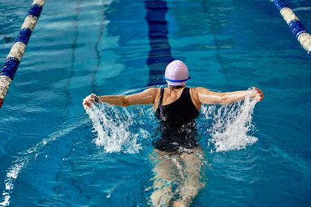 Sportlerin schwimmt im Schmetterlingsstil. Wasserspritzer zerstreuen sich in verschiedene Richtungen.