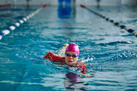 Female athlete swimming fast in crawl style. Splashes of water scatter in different directions. Imagens