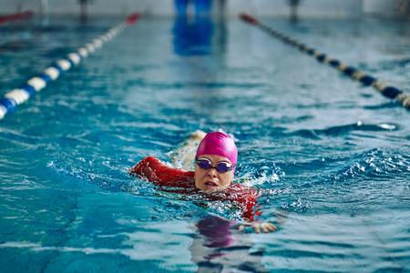 Vrouwelijke atleet die snel in kruipstijl zwemt. Spatten water verspreiden zich in verschillende richtingen. Stockfoto