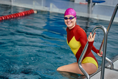 Portrait of a smiling woman swimmer in red yellow swimsuit in the pool after the completion of training.