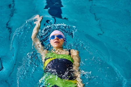 Female athlete in a green-black swimsuit is swimming on his back. Splashes of water scatter in different directions.