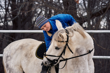 Young woman rider in a blue blazer and sporting a cap for a walk on a white horse on a cloudy winter day.  A woman is feeding a horse with her arms.