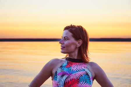 Portrait of a red-haired wet middle-aged woman in a swimsuit on a summer evening after sunset.. Close-up.