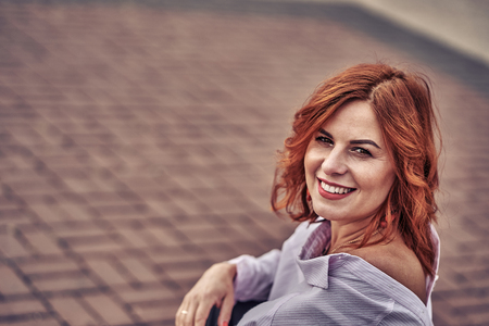 Portrait of a smiling middle-aged woman with red hair..  Close-up.