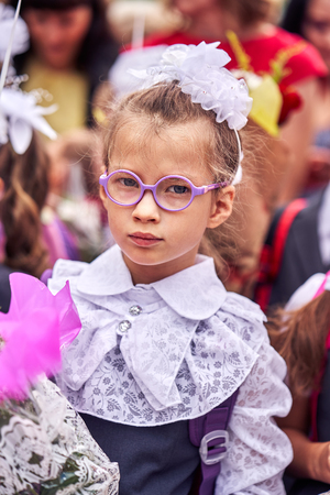 A girl child in school festive uniform with bows, glasses and a school bag on her back is standing in a crowd of children and is awaiting the start of the opening ceremony of the new school year. Close-up. Standard-Bild