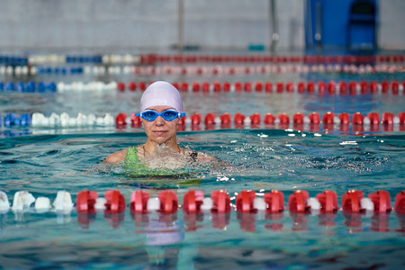 Female swimmer emerges from the water. She finished training swims in the pool. Close-up.
