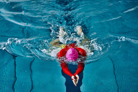 Female athlete in a red-yellow swimsuit is swimming in the style of breaststroke. Splashes of water scatter in different directions.
