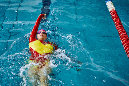 Female athlete in a red-yellow swimsuit is swimming on his back. Splashes of water scatter in different directions. 免版税图像