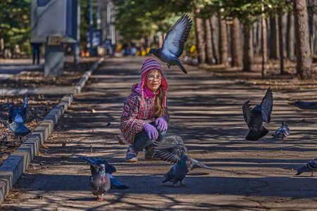 Girl in a red jacket, hat and glasses chasing pigeons in the park. A girl walks along a park alley on a sunny spring day.