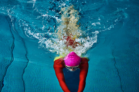 Female swimmer in a red suit and glasses sunk into the water to make a U-turn.Splashes of water scatter in different directions. Stock Photo