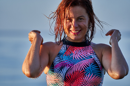 Portrait of a red-haired wet laughing woman of middle age in a swimsuit on a summer evening in the light of the setting sun. Close-up. 스톡 콘텐츠