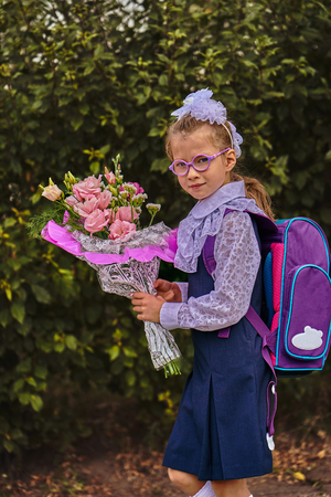 A girl child in school uniform with bows, glasses and a school bag on his back goes to the first class of the school on September 1st. The girl is holding a bouquet of flowers. Close-up.
