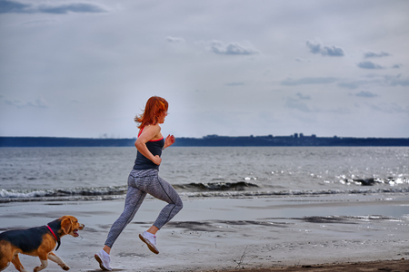 A red-haired middle-aged woman in sportswear runs along the sandy shore of a large river with her puppy on a cloudy summer morning. Healthy lifestyle.