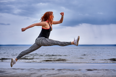 A middle aged woman with red hair jumps while jogging. A woman practices gymnastics on the sandy bank of a large river. Cloudy spring morning. Фото со стока