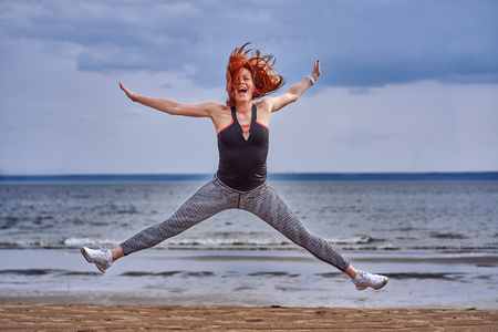 A middle aged woman with red hair emotionally makes the jump. A woman practices gymnastics on the sandy bank of a large river. Cloudy spring morning. Stock Photo - 123611974