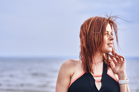 Portrait of a middle-aged woman with red hair walking along the river bank. Sunny spring morning. Close-up. Фото со стока