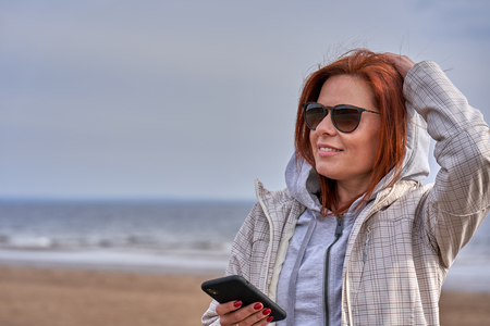 Portrait of a red-haired middle-aged woman in sunglasses and a raincoat looking at a smartphone. Sunny spring morning. Close-up.