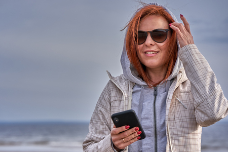 Portrait of a red-haired middle-aged woman in sunglasses and a raincoat holding a smartphone in her hand. Sunny spring morning. Close-up.