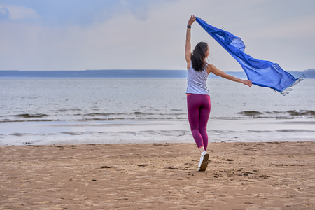Young slim brunette woman in sportswear doing sport dancing with a blue scarf. A woman is engaged on the sandy shore of a large river. Cloudy summer morning. Фото со стока