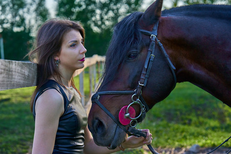 A young brunette woman in a black dress communicates with a dark brown horse on a sunny summer evening. Evening walk with a horse. Close-up.