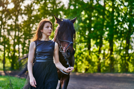A young slim brunette woman in a black dress is walking along the road and leading a dark brown horse on a leash. Sunny summer evening. Close-up.