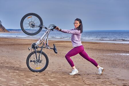 Young slim brunette woman on a bike ride on the sandy shore of a large river. Cloudy summer day.