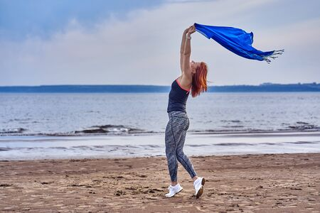 Slim red-haired middle-aged woman in sports form is engaged in dancing with a blue scarf. A woman is engaged on the sandy shore of a large river. Cloudy summer morning.