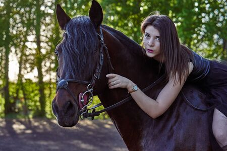 Young slim woman brunette in a black dress sitting on dark brown horse. Sunny summer evening. Close-up.