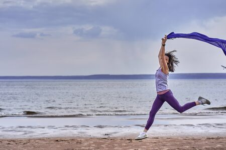 Young slim brunette woman jumping while jogging while holding a blue scarf in her hands. A woman is engaged in gymnastics in the spring morning on the sandy bank of a large river. Cloudy morning.