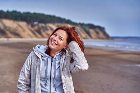 Portrait of a laughing middle-aged woman with red hair walking along the river bank. Sunny spring morning. Close-up. Reklamní fotografie