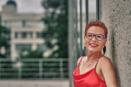 Portrait of a red-haired laughing middle-aged woman in a red blouse standing against the wall. Cloudy summer day. Close-up. Stock fotó