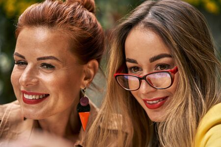A middle-aged red-haired woman in a brown coat and a brown-haired young woman in a yellow coat and with glasses  are sitting in a summer street cafe and choose food and drinks from the menu. Фото со стока