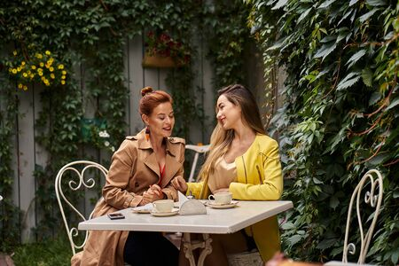 A middle-aged red-haired woman in a brown coat and a brown-haired young woman in a yellow coat are sitting in a summer street cafe and  talking to each other.