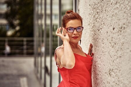 Portrait of a red-haired laughing middle-aged woman in a red blouse standing against the wall. Cloudy summer day. Close-up. Фото со стока