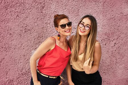 A red-haired laughing middle-aged woman in a red blouse and glasses and a young laughing woman with brown hair in a golden blouse and glasses are standing against a pink concrete wall.