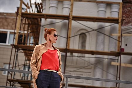 Portrait of a red-haired middle-aged woman in a red blouse, in a brown cloak and in glasses  while walking around the city. Cloudy summer day. Close-up.