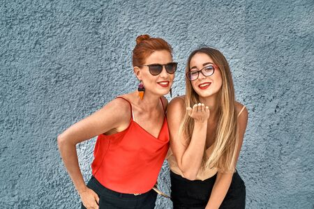 A red-haired laughing middle-aged woman in a red blouse and glasses and a young laughing woman with brown hair in a golden blouse and glasses are standing against a concrete wall.